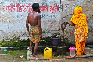 <p>A husband and wife fill up water containers from a tube well in Bangladesh. Photo by Laura Wright.</p>