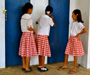 <p>Three school girls peaking in a school latrine in the Philippines.</p>